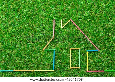 Colorful house icon on green field for real estate concept