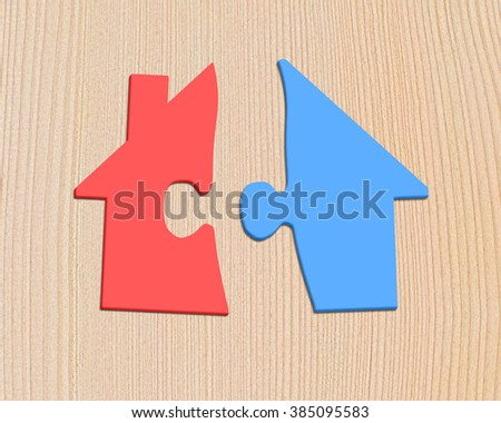 Colorful house shape puzzles, on wooden background.
