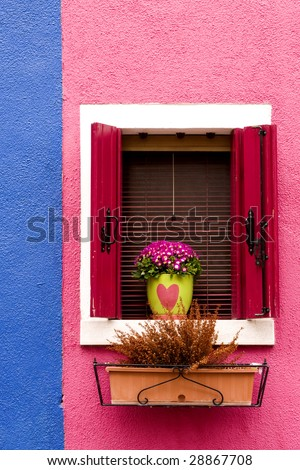 Colorful house with window, shutters flowers and plants
