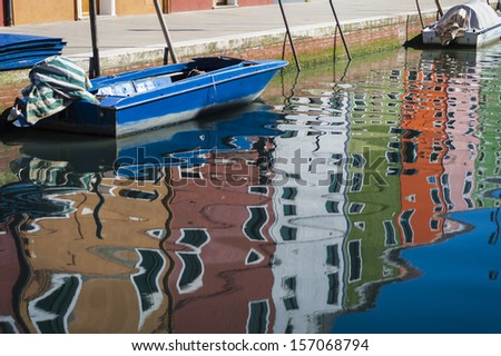 Colorful houses and a boat, with reflections in the canal, Burano, Italy, near Venice