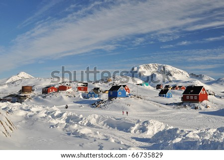 Colorful houses and two walking persons in the Kulusuk village, Greenland - stock photo