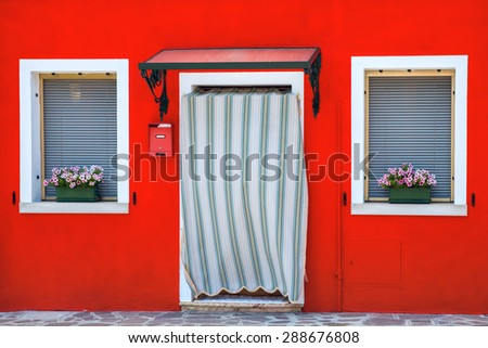 Colorful houses decorated with flowers, windows with shutters, close-up, famous island Burano, Venice, Italy - stock photo