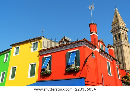 Colorful houses in a row on Burano Island in the Venetian lagoon, Venice, Italy. On the right the leaning bell tower of Saint Martin Church.