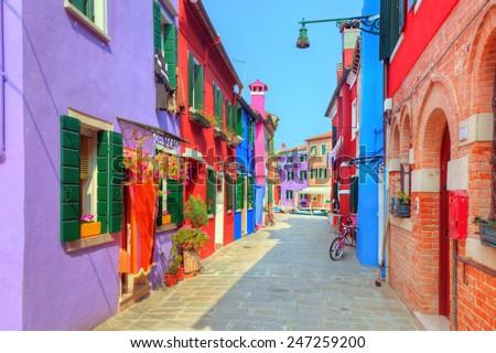 Colorful houses on Burano island, near Venice, Italy. Charming street. Sunny day. - stock photo