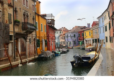 Colorful  houses on the Italian island of Burano showing boats with geese on the canal in the rain - stock photo
