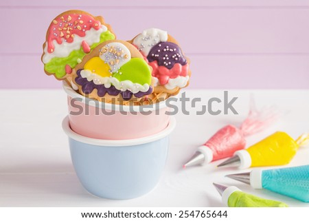 Colorful ice cream cone shape icing cookies on white background and cornets with glaze for painting - stock photo
