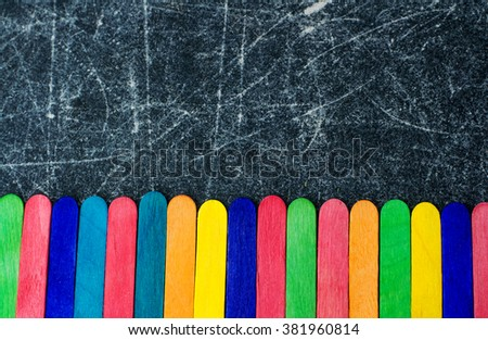 Colorful ice cream sticks on a chalkboard background space for text - stock photo