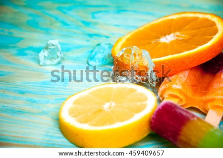 Colorful ice lolly and friuts on blue wooden background