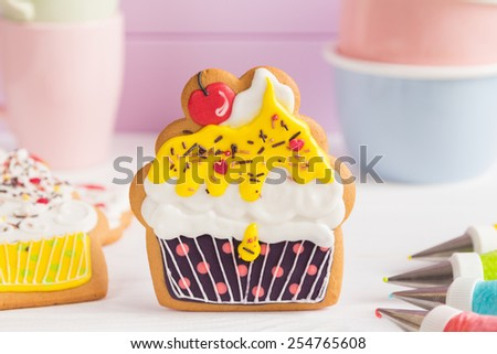 Colorful icing cookies in cupcake shape on white background and cornets with glaze for painting - stock photo