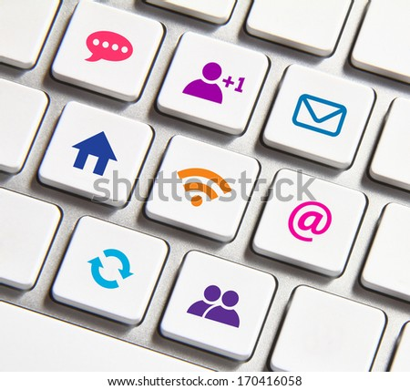Colorful icons on the white keyboard. - stock photo