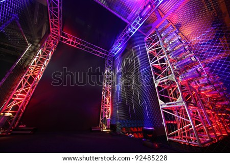 Colorful illuminated way with grid to boxing ring inside fight club; many lights - stock photo