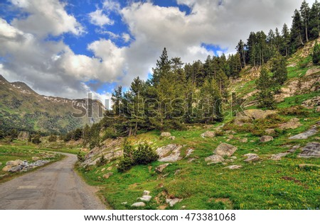 Colorful image of a mountain valley with forests and snowy hills near Benasque in the Pyrenees, Spain