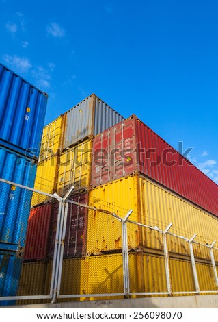 Colorful industrial cargo containers are stacked under blue cloudy sky behind metal fence with barbed wire. Vertical photo - stock photo
