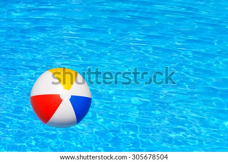 Colorful inflatable ball floating in swimming pool - stock photo