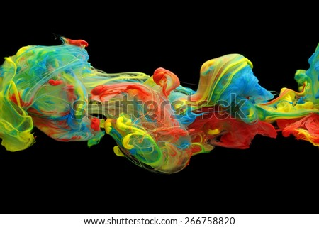 Colorful ink and paint swirling through water - stock photo