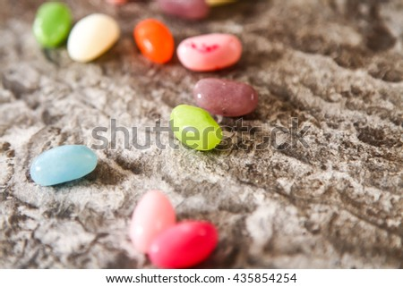 Colorful Jelly Beans (close-up shot) on background stone - stock photo