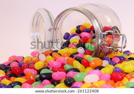 Colorful Jelly Beans Scattered from Spilled Glass Jar On - stock photo