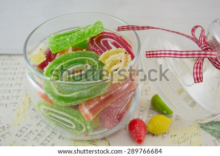 Colorful jelly rolls in a decorated glass  jar on a decoupage decorated table - stock photo