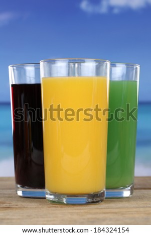 Colorful juices like orange and cherry juice in glasses