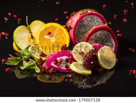 Colorful juicy assortment of sliced tropical fruits (purple dragon fruit, orange, lemon, pomegranate seeds, green apple and mint), on a wet black table with splashes of water - stock photo
