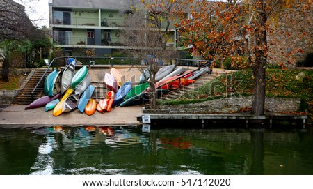 Colorful kayak boats align on river shore in front of old apartment building