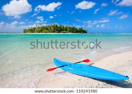 Colorful kayak in a tropical lagoon with small island on background - stock photo