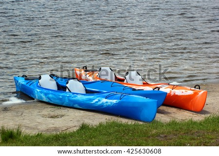 Colorful kayaks and canoes on sandy beach - stock photo