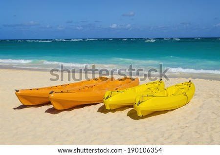 Colorful kayaks on sandy exotic beach and azure ocean water background - stock photo