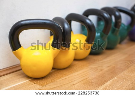 Colorful kettle bells on the floor in the gym - stock photo