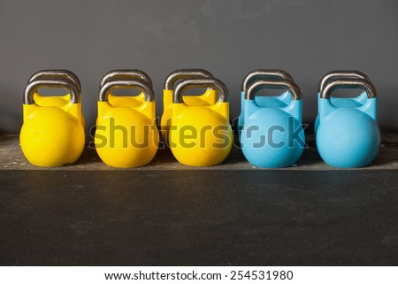 colorful kettlebells in a row in a gym - stock photo
