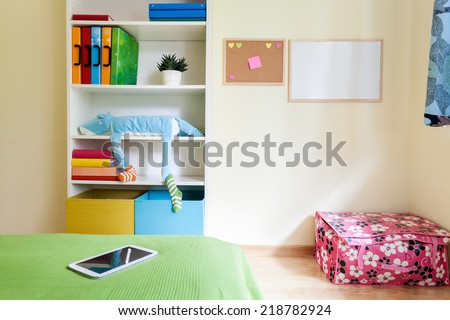 Colorful kids room with comfortable bed and white bookcase - stock photo
