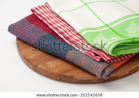 Colorful kitchen towels on a kitchen wooden board.