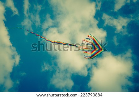 colorful kite flying on blue sky - stock photo