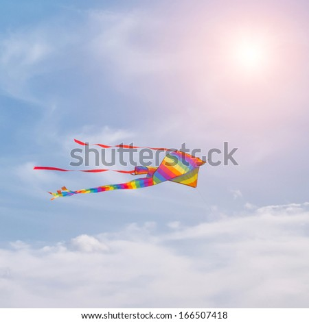 Colorful kite in cloudy sky with sun