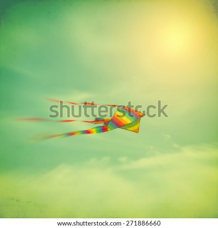 Colorful kite in cloudy sky with sun, retro toned with texture overlay, motion blur - stock photo