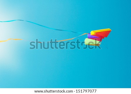 Colorful kite on the blue cloudless sky