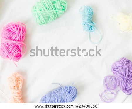 Colorful knitting wool on white fabric background. - stock photo