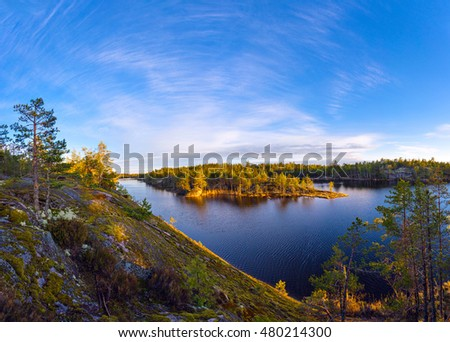 Colorful landscape of granite slope with pine trees, calm lake and beautiful blue sky at sunset sunlight. Karelia Republic, Russia.