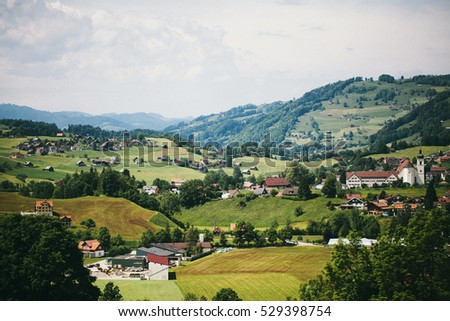 Colorful landscape view in Switzerland, alpine green. Sky with clouds. Houses and churches.