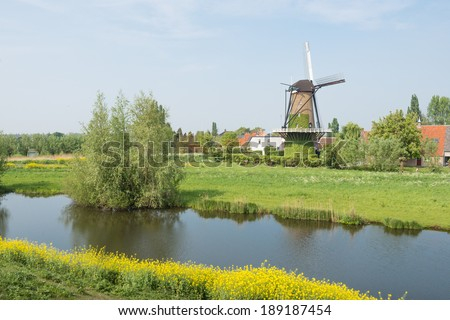 Colorful landscape with an historic windmill in the small Dutch village of Terheijden. - stock photo
