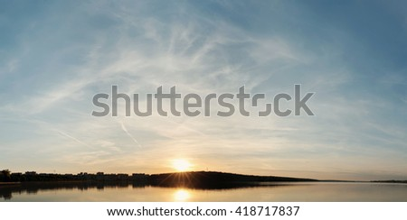 colorful landscape with water and cloudy sky at sunset