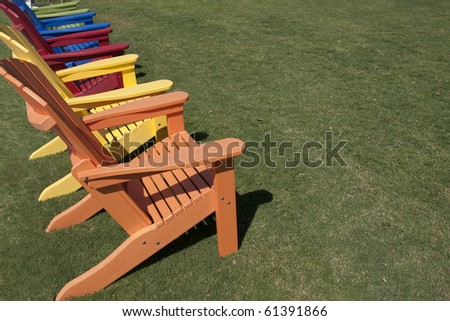 colorful lawn chairs sitting on green grass - stock photo