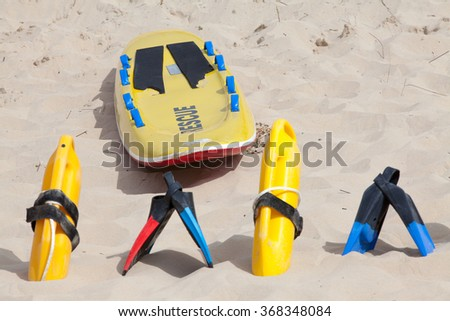 Colorful lifesaving equipment lying on the beach sand in the hot summer sun - stock photo