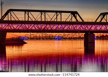 Colorful light rail bridge with an old train bridge behind it across the river at sunset - stock photo