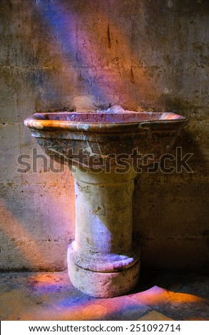 Colorful light spots on the holy water stoup, the tiled floor and the wall in the church. Sunlight filtered through the stained glass window. - stock photo