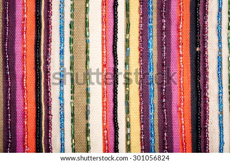 Colorful lined fabric with beads texture background   - stock photo