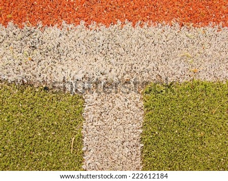 Colorful lines in empty outdoor handball playground, plastic light green surface on ground and white, red and blue bounds lines.  - stock photo