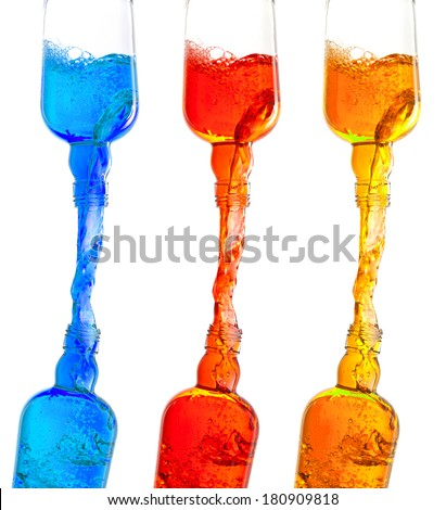 Colorful liquids flow from bottles  - stock photo