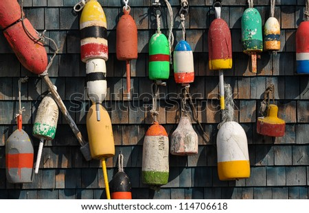 Colorful lobster floats hanging on a weathered clapboard lobster man shack on a working Maine Dock - stock photo