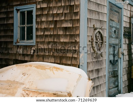 Colorful lobsterman shack with well worn and weathered shingles